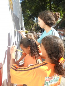 Crianças e educadores pintando os muros da comunidade