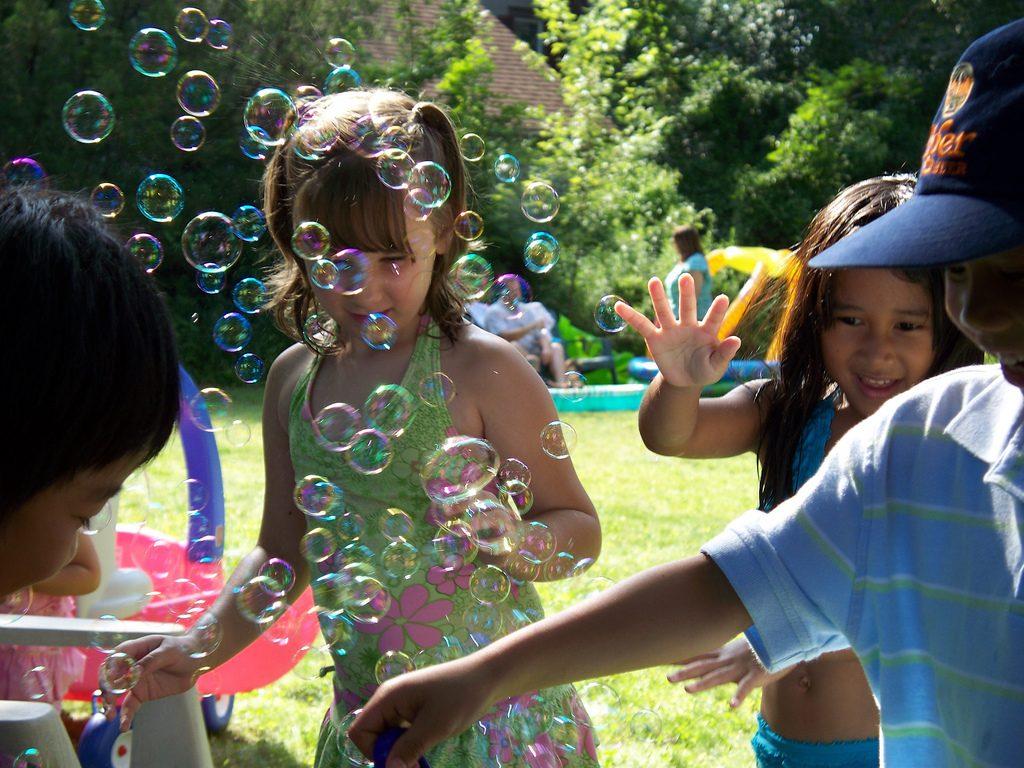 Crianças soltam bolhas de sabão em parque; celebração da infância