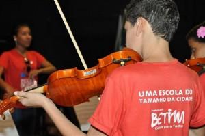 Crianças do programa em apresentação de violino. Foto: Reprodução