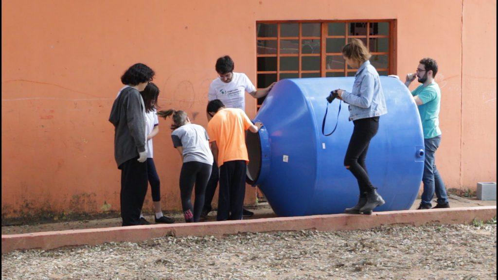 Crianças observam uma cisterna de plástico, deitada no chão