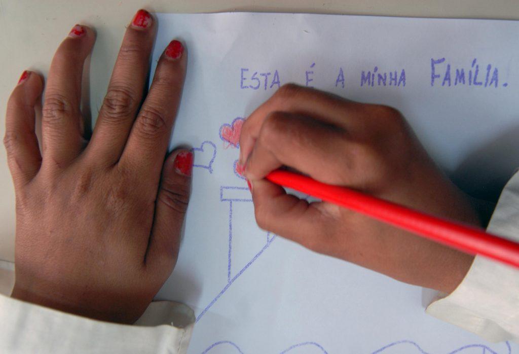 Menina escrevendo e desenhando em papel