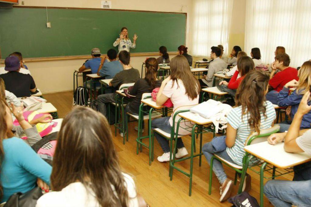 Sala de aula, com alunos sentados em carteiras, e professora dando aula