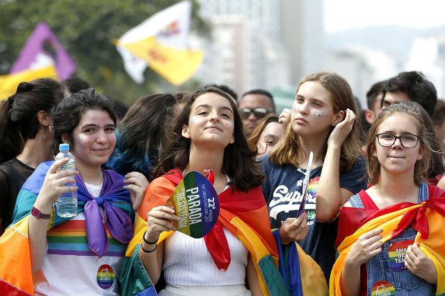 Grupo de meninas, vestindo bandeira LGBT, caminham durante a parada LGBT, pelo respeito à diversidade de gênero e de identidades