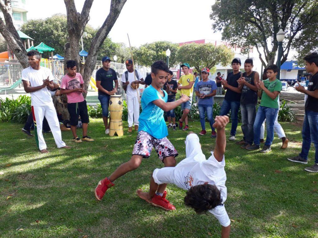 Alunos jogam capoeira em praça próxima à escola