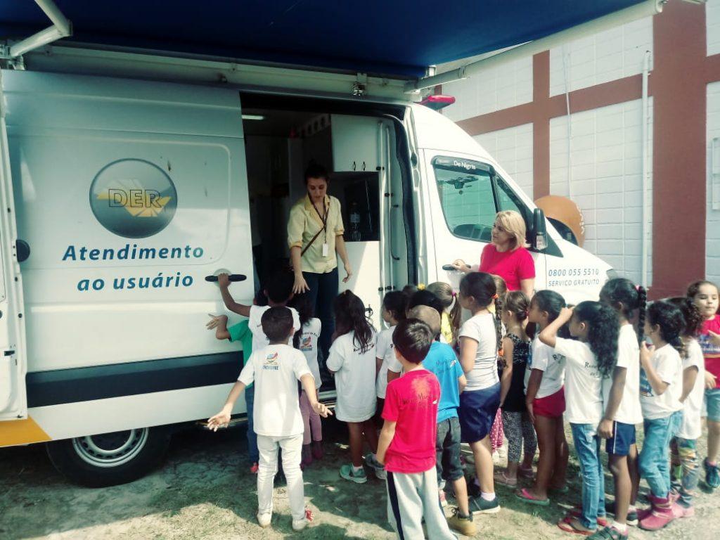 Agente do Departamento de Estradas de Rodagem (DER) conversa com as crianças