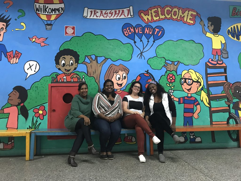 Eliane, Juliana, Camilla e Mariana, em frente a um mural feito pelos estudantes